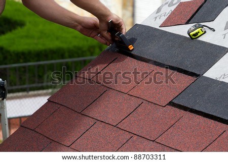 Placement of asphalt shingles - stock photo