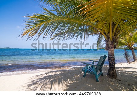 Placencia, Belize, Central America - July 7, 2016: Empty Beach Sun Chair shaded under a palm tree on the beach.