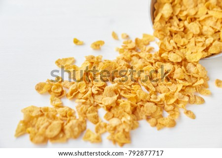 Placer of cornflakes with a metal bowl on a painted white wooden background. Cornflakes scattered on a wooden table.