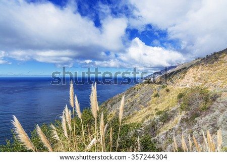 Placid blue seas, off shore, along a rocky coastline, blue sky & white cloud covered mountain tops, aquamarine waters, traveling the Big Sur Highway (Highway 1), on the California Central Coast. - stock photo