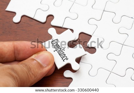 Placing missing a piece of puzzle with compliance word - stock photo