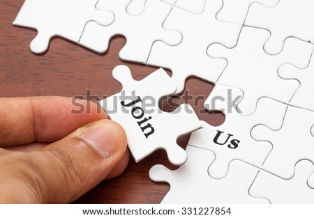 Placing missing a piece of puzzle with join us words - stock photo
