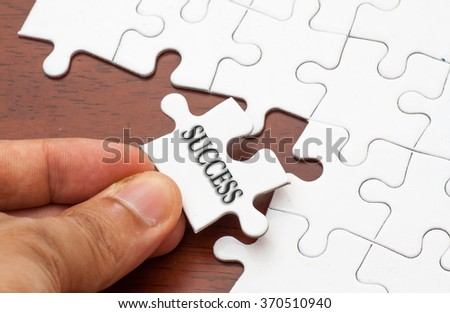 Placing missing a piece of puzzle with success word written.
