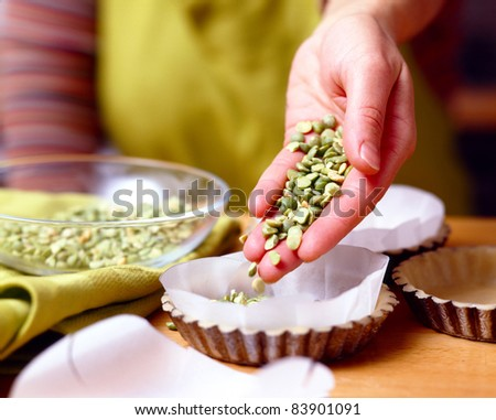 Placing the dried beans on the wax paper in the molds - stock photo