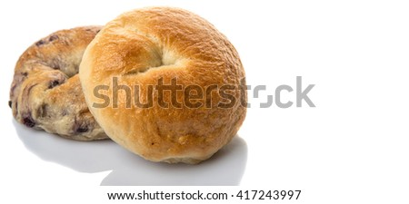 Plain bagel and blueberry bagel over white background