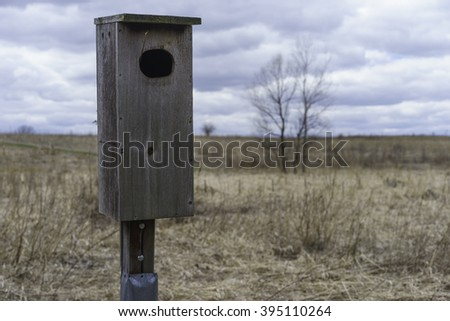 Plain birdhouse above prairie grass on a cloudy day, March in northern Illinois, USA, for themes of conservation, habitat, the environment (foreground focus) - stock photo