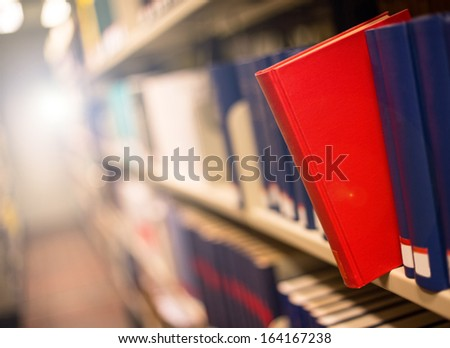 plain book jut out a bookshelf with light in the back - stock photo