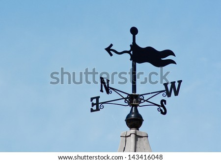 plain modern weathervane on a roof top showing wind direction without a cockerel - stock photo
