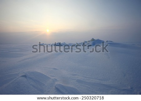 Plain of snow, ice and low Northern sun - stock photo