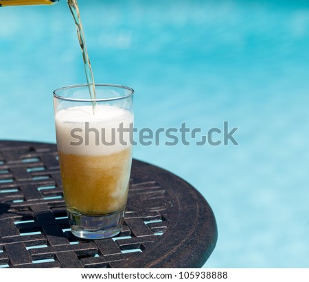 Plain pint glass of beer being poured sitting on table by blue swimming pool - stock photo