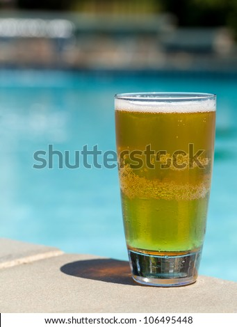 Plain pint glass of cold lager beer sitting on edge of blue swimming pool - stock photo