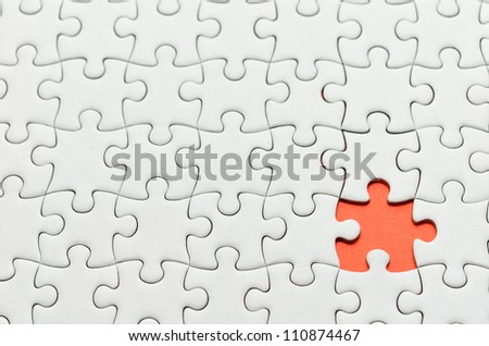Plain white jigsaw puzzle, on orange background.