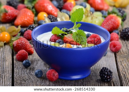 Plain yogurt with mixed fresh fruit in a blue ceramic bowl - stock photo