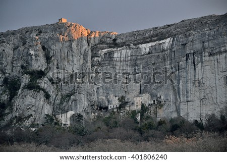 PLAN-D'AUPS-SAINTE-BAUME, FRANCE - JANUARY 6, 2016 : Chapel of Saint-Pilon into the sunset overhanging Marie-Madeleine cave and the massif of the Sainte-Baume. - stock photo