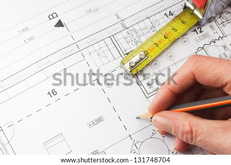 Plan of a house with a ruler and a hand writing with a pencil - stock photo
