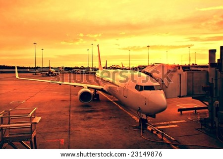 Plane at Melbourne Airport Terminal at Sunrise - stock photo