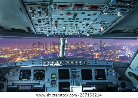 plane cockpit and the city of night - stock photo