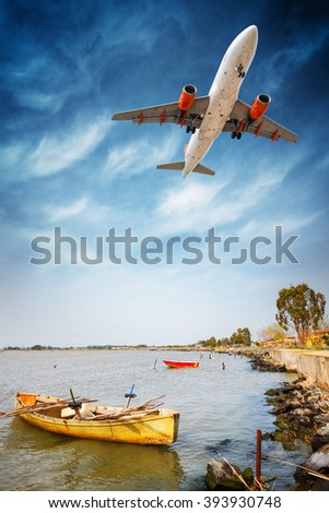 Plane flying low over the lagoon to land at the airport - stock photo