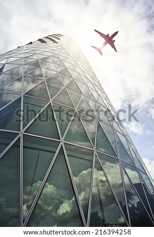 plane flying over a modern glass and steel office tower in the Westhafen district of Frankfurt am Main, Germany - stock photo