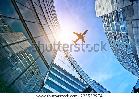plane flying over modern glass and steel office buildings near Potsdamer Platz, Berlin, Germany - stock photo