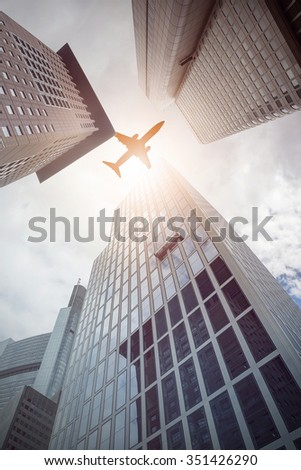 plane flying over office buildings, Frankfurt am Main, Germany - stock photo