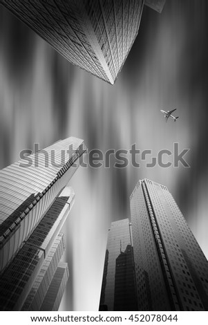plane flying over the skyscrapers - stock photo