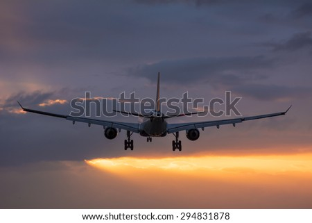 Plane flying towards the runway during a cloudy sunrise.