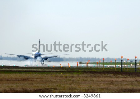 Plane has just landet in an airport. Note the picture is in blur because of the heat from the engine and the smoke from the wheels. - stock photo
