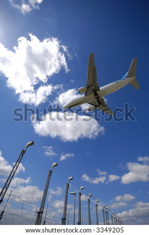 Plane is flying over landing lights at the airport. Wide angel shot. - stock photo