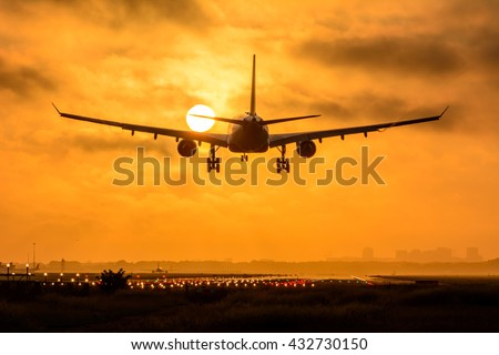 Plane is flying to the airport during a foggy sunrise. Nice vortex behind the wings of the airplane. - stock photo