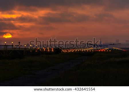 Plane is flying to the airport. Foggy sunrise sky during the early morning landing. - stock photo