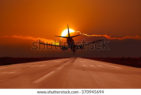 Plane landing in a sunset - stock photo