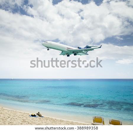 Plane landing over Maho Beach in Saint Martin island - stock photo
