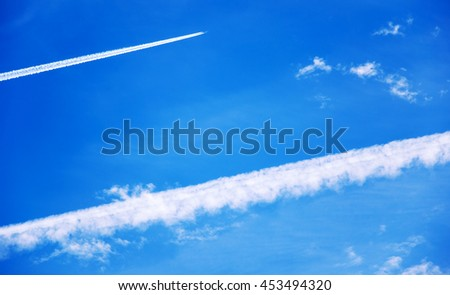 Plane leaves diagonal trail in the blue sky