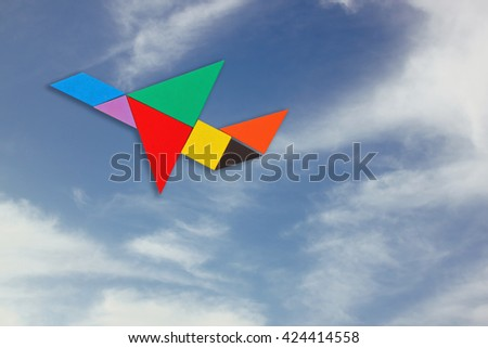 plane made from tangram puzzle. sky background