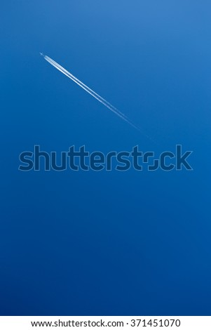plane on a blue sky with white tail of condensation trace