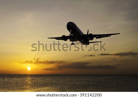Plane on blurred color of the sunset in twilight