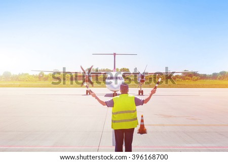 Plane on tarmac in the airport, guided by ground staff. Taxiing