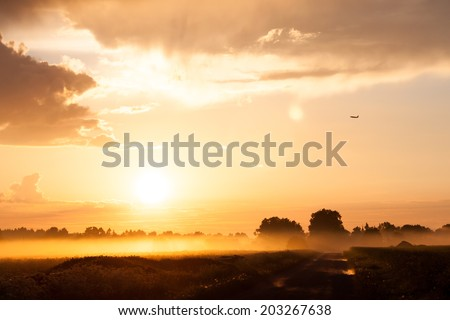 Plane over rural countryside field in fog fog, with forest at the background. Red sunset - stock photo