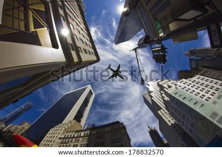 Plane over skyscrapers, New York City - stock photo