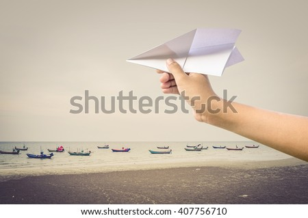 plane paper in children hand over sea and boats, vintage style - stock photo