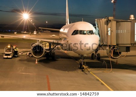 plane parked at the airport at night - stock photo