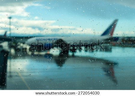 Plane silhouette of the covered glass raindrops. Flights transferred to a later time because of bad weather. - stock photo