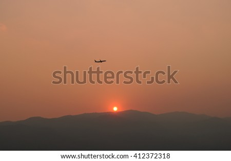 Plane take off over mountain while sunset. - stock photo