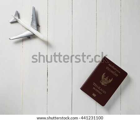 Plane travel on white wooden table with Passport.