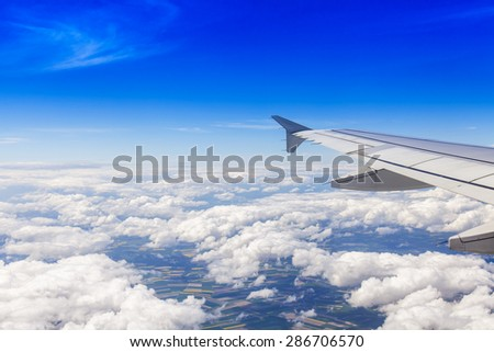 Plane view from the window on picturesque white clouds