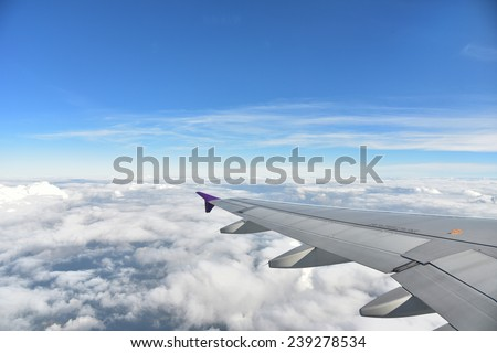 Plane window with blue sky and clouds outside - stock photo