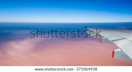 Plane wing and sky with copyspace, panoramic view, travel concept - stock photo