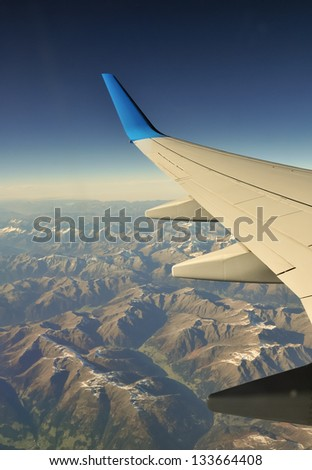Plane wing over Alps somewhere between Switzerland and Austria - stock photo