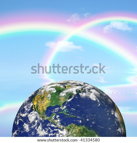 Planet earth against a background of double rainbows and a blue sky with reflection over rippled water. - stock photo